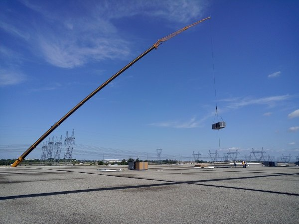 Cranes hoisting refrigeration system to top of large warehouse roof
